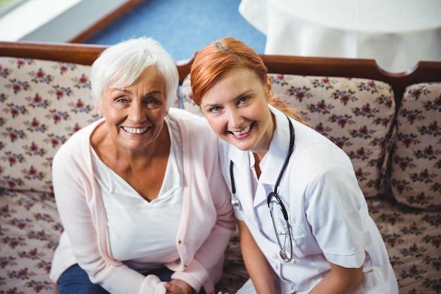 年配の女性と看護師のカメラに笑顔