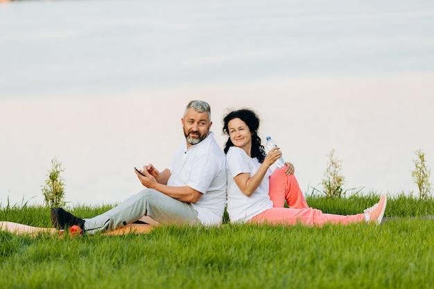 年配の女性と草の上に座っている年配の男性。携帯電話を保持しているイヤホンで水のボトルと男を保持している女性
