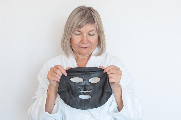 Старшая женщина наносит на лицо черную косметическую маску. анти-возрастная концепция. лицо зрелой женщины после санаторно-курортного лечения. бьюти-санаторно-курортное лечение. клиника пластической хирургии, косметология, новый сеньор