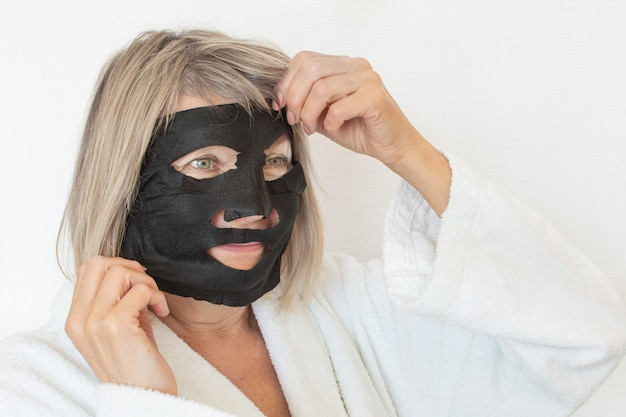 Senior woman applies a black cosmetic mask to her face. anti age concept. mature woman face after spa treatment. beauty spa treatment. plastic surgery clinic, cosmetology, new senior