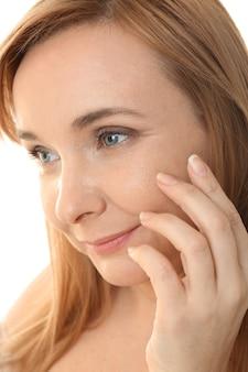 Старшая женщина, применяющая антивозрастной крем на лице, крупным планом