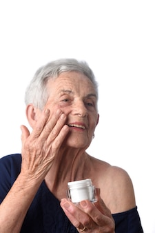 Senior woman applying skin cream or moisturiser to her face