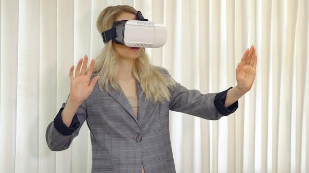 Старшая женщина-архитектор или клиент, использующий очки vr, чтобы представить или разработать проект, стоящий в офисе.