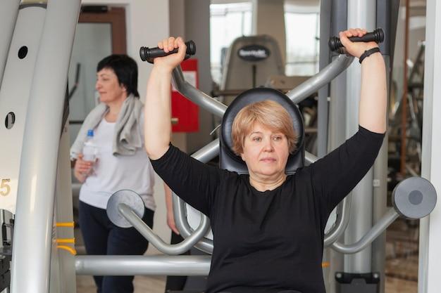 Старшая женщина на спортзале разрабатывая