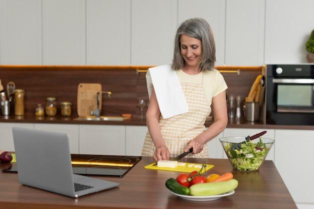 Старшая женщина дома на кухне, принимая уроки кулинарии на ноутбуке
