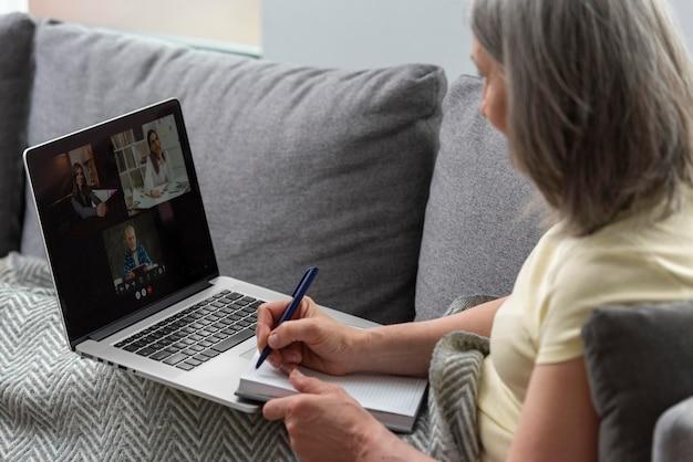 Старшая женщина дома на диване, используя ноутбук и делая заметки