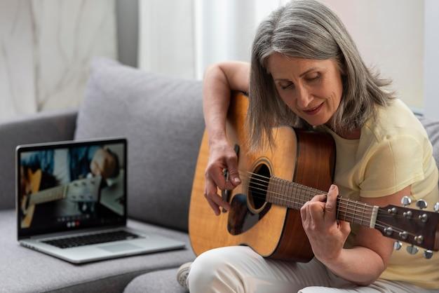 Старшая женщина дома на диване, используя ноутбук для уроков игры на гитаре