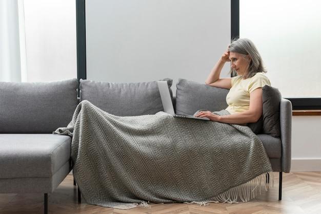 Старшая женщина дома на диване, используя ноутбук