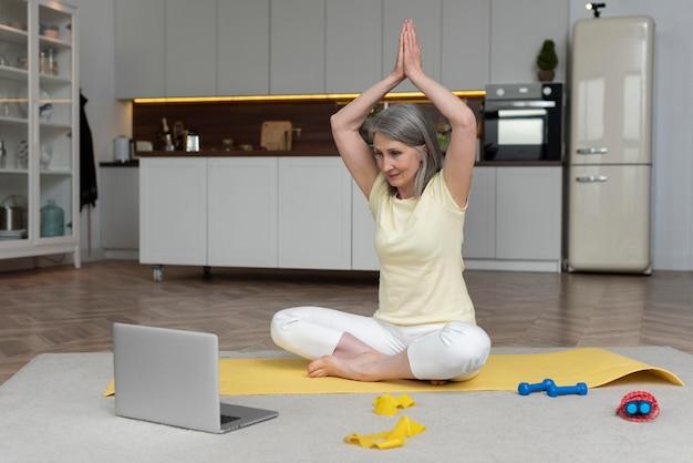 Старшая женщина дома, принимая урок фитнеса на ноутбуке