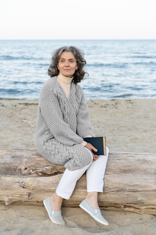 本を持ってビーチで年配の女性