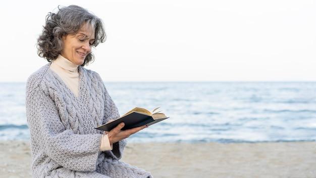Старшая женщина на пляже, читая книгу
