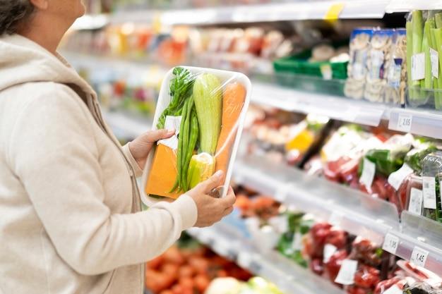 Старшая женщина в супермаркете, проверяя продукт перед покупкой