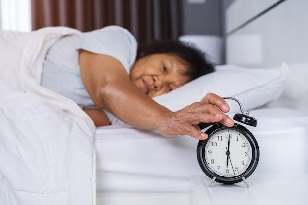 Senior woman in bed pressing snooze button on early morning alarm clock