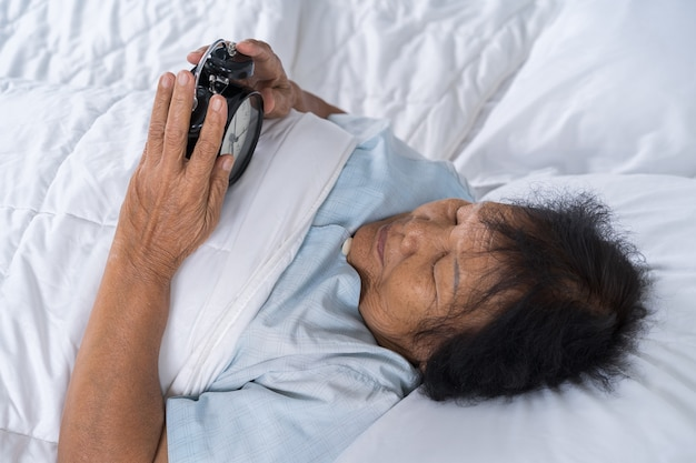 Senior woman in bed pressing snooze button on morning alarm clock