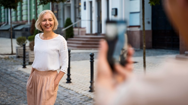 Senior woman being photographed by partner with smartphone outdoors