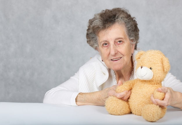 Пожилая женщина от 70 до 80 лет сидит с плюшевым мишкой за столом. крупным планом