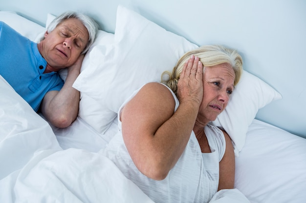 Senior woman blocking ears while man snoring
