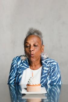 彼女の誕生日のお祝いにケーキにろうそくを吹く年配の女性