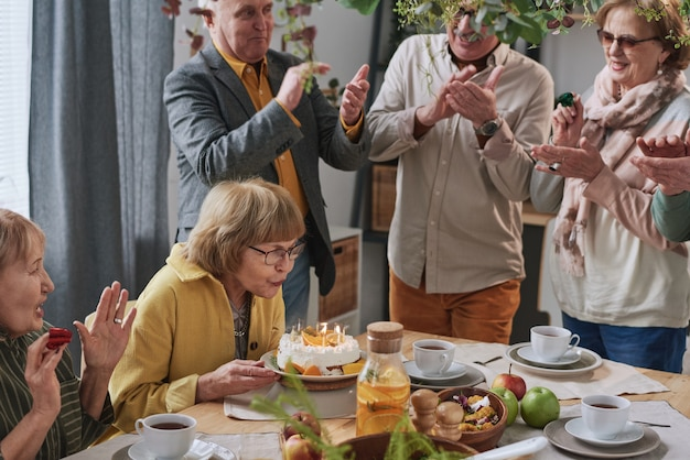 Senior woman blowing candles on her birthday cake while her friends clapping hands and congratulating her at party