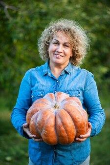 Senior woman in a blue shirt holds a pumpkin in the garden