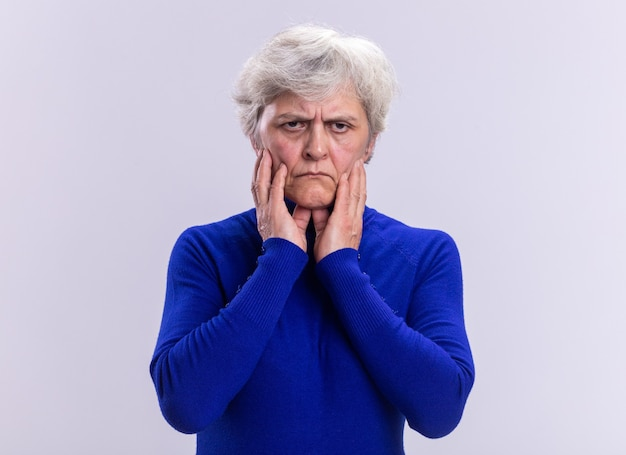Senior woman in blue turtleneck looking at camera with frowning face standing over white background