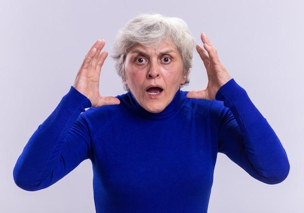 Donna anziana in dolcevita blu che guarda la telecamera preoccupata e frustrata con le mani alzate in piedi sopra il bianco