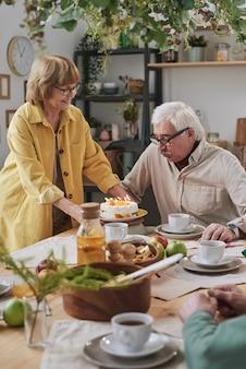 自宅の食卓に座っている夫のためにバースデーケーキを持って来る年配の女性