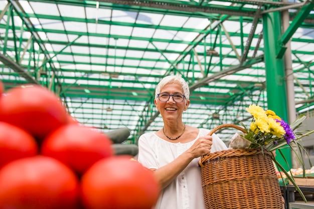 Senior woman buying fresh organic vegetable on market