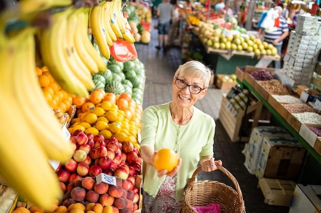 Старшая женщина покупает свежие овощи и фрукты на рынке и держит сумку, полную здоровой пищи