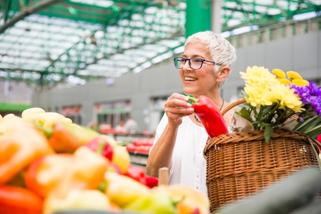 Senior woman buying red peppers at the market