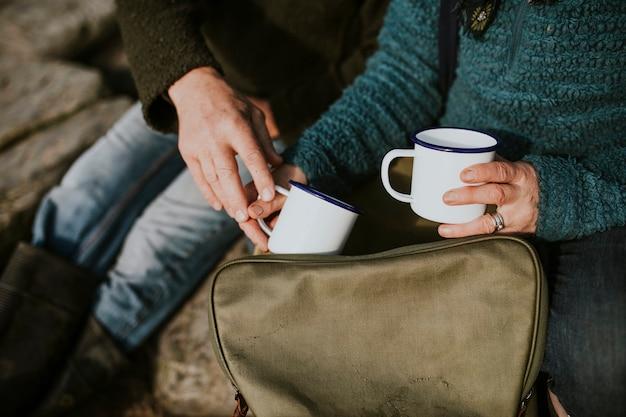 디자인 공간이 있는 커피잔을 들고 있는 시니어 여성 캠핑카
