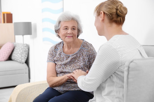 Senior woman and caregiver sitting on sofa at home