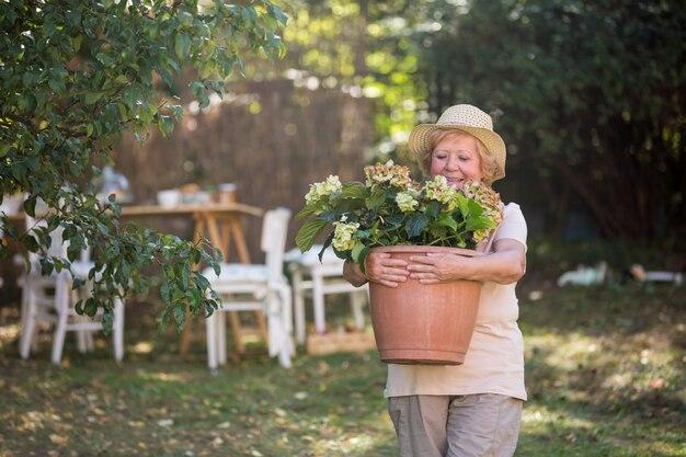 庭の鉢植えを運ぶ年配の女性