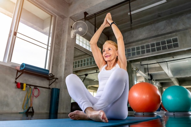 Senior woman caucasian doing yoga exercise at fitness gym.