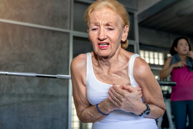 Senior woman caucasian heart attack during training at fitness gym.