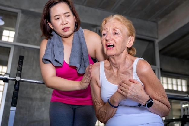 Senior woman caucasian heart attack during training with asian friend at fitness gym.