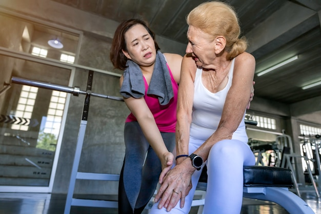 Senior woman caucasian leg pain during training with asian friend at fitness gym.