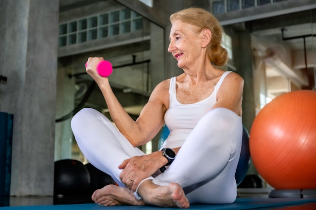 Senior woman caucasian training arm with dumbell at fitness gym.