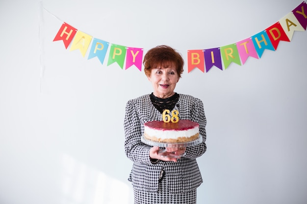 Senior woman celebrating her birthay at home. holding birthday cake over white background
