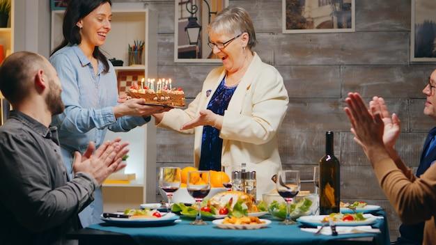 가족과 함께 생일을 축하하는 고위 여자. 친구 및 가족과 함께 모일 때 맛있는 케이크. 슬로우 모션 촬영