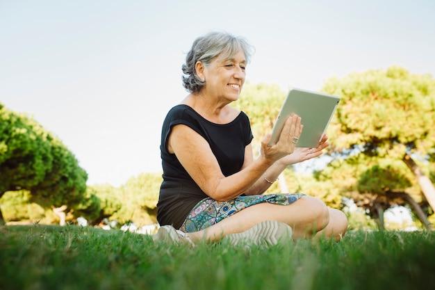 Старшая женщина разговаривает онлайн со своим планшетом в парке