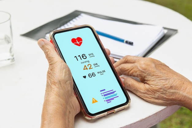 Senior woman checking blood pressure (hypertension) vai mobile phone