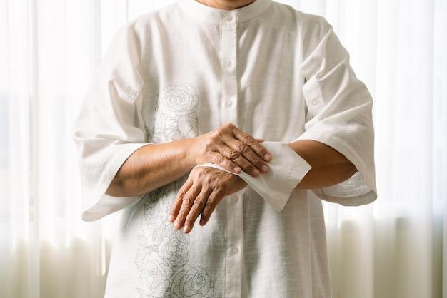 白い柔らかいティッシュペーパーで手を掃除する年配の女性。白い背景で隔離