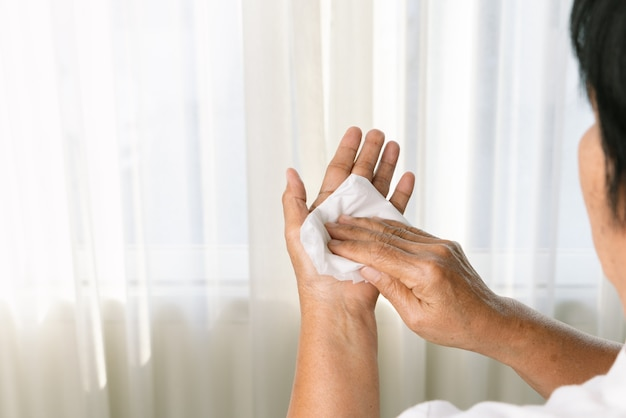 흰색 부드러운 휴지로 그녀의 손을 청소하는 고위 여자. 흰색 배경에 고립