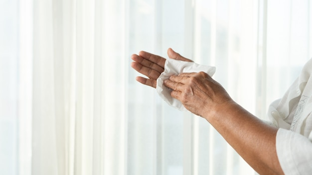 Senior woman cleaning her hands with white soft tissue paper.