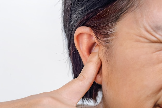 Senior woman closes ears with fingers to protect from loud noise