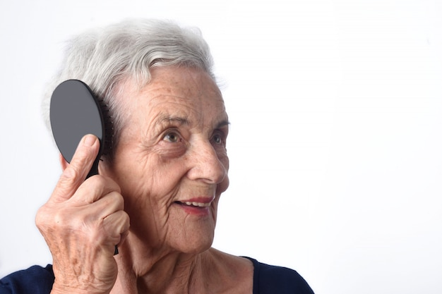Senior woman combing her hair on white background