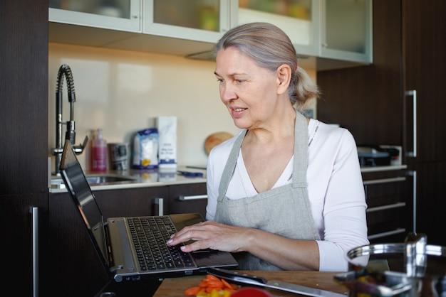 Старшая женщина готовит с помощью рецепта на ноутбуке.