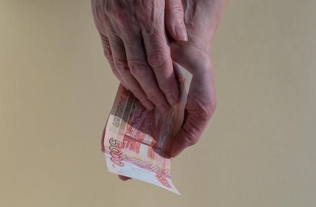 시니어 여자는 15,000 루블 지폐의 지폐 손과 돈을 센다