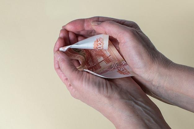 노인 여성은 루블 지폐의 15000 지폐를 세다 노령 연금
